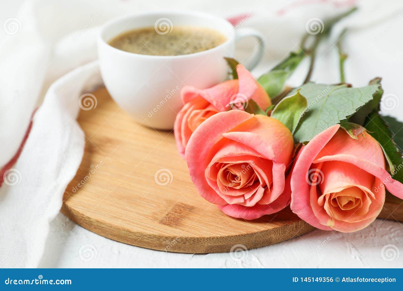 Composición con la taza de café, de rosas y de toalla de cocina en el fondo blanco