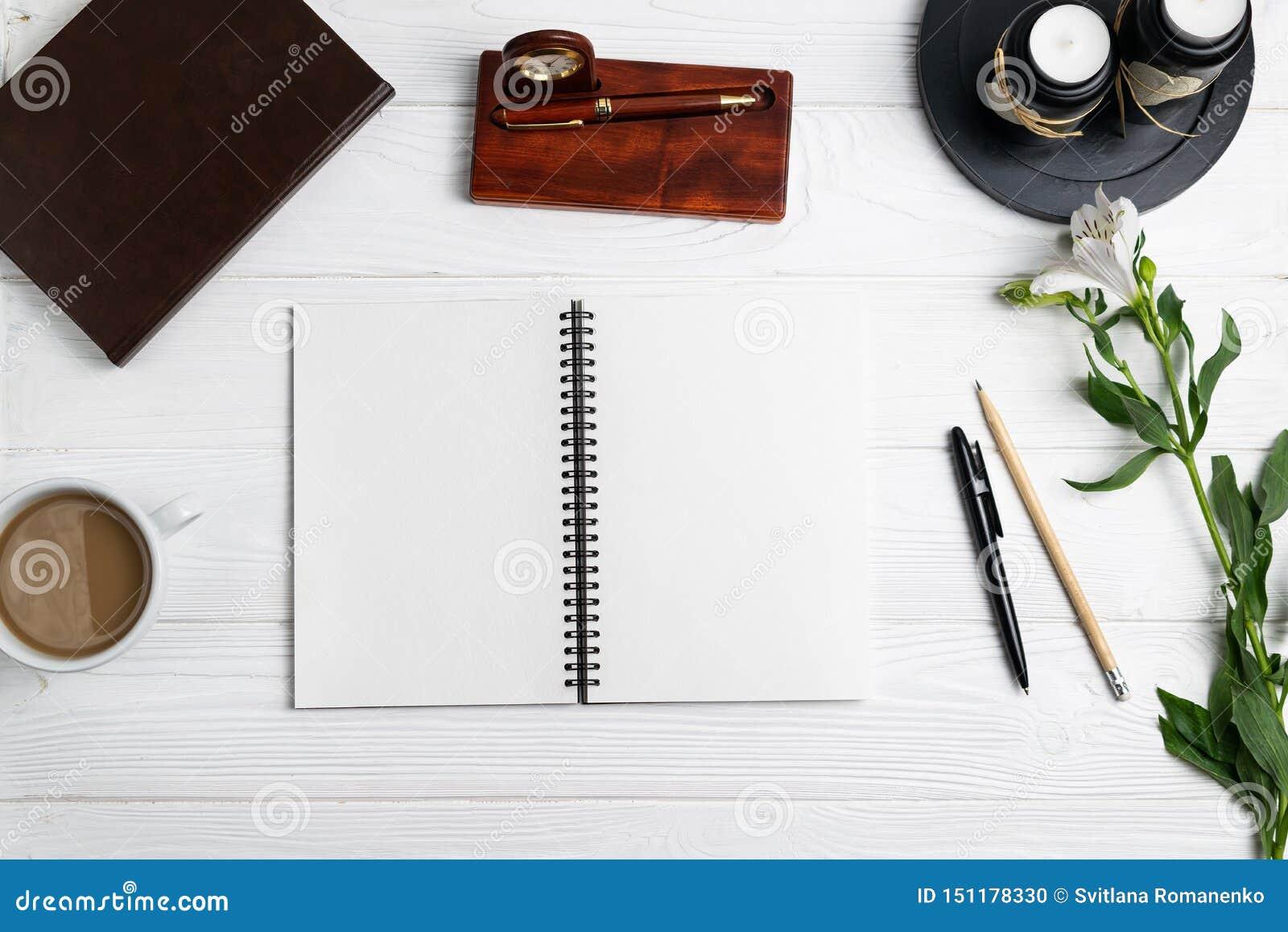 Composición con las flores inmóviles del café del lápiz de la pluma del cuaderno de la educación de la oficina