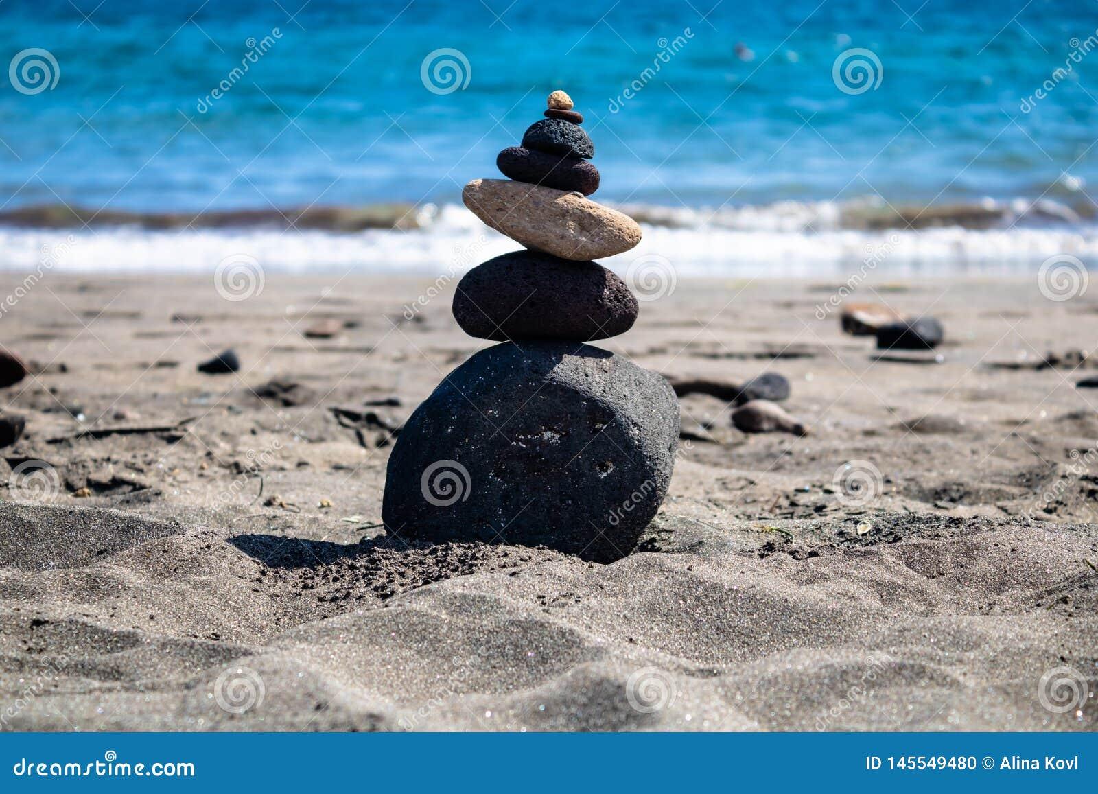 Composición de equilibrio en la playa con el fondo azul del océano - imagen de las piedras