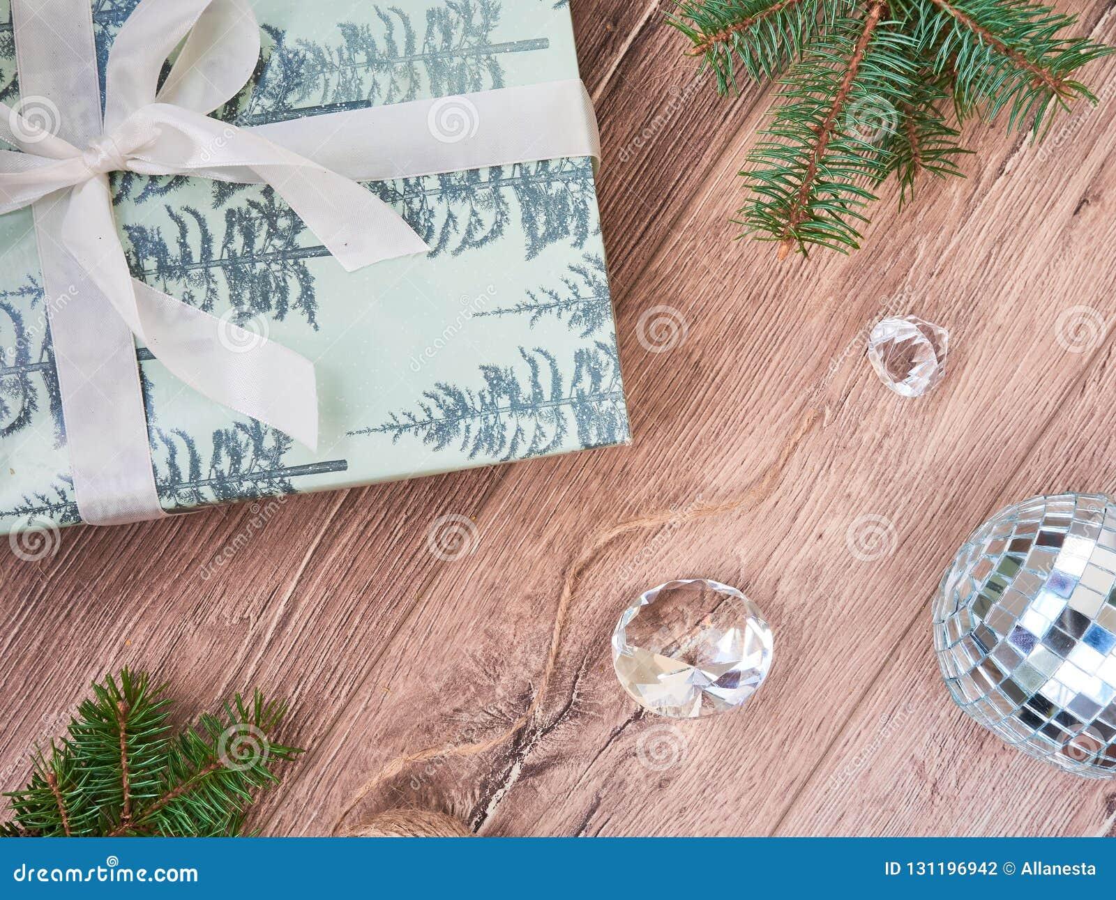 Composición de la Navidad Regalos de la Navidad, decoraciones de las ramas de árbol de abeto, negras y de oro en el fondo blanco