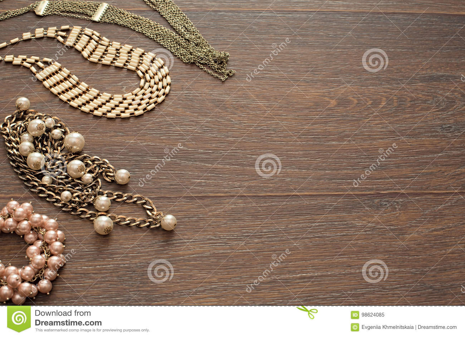 Composición decorativa de la joyería del ` s de las mujeres en fondo oscuro de madera