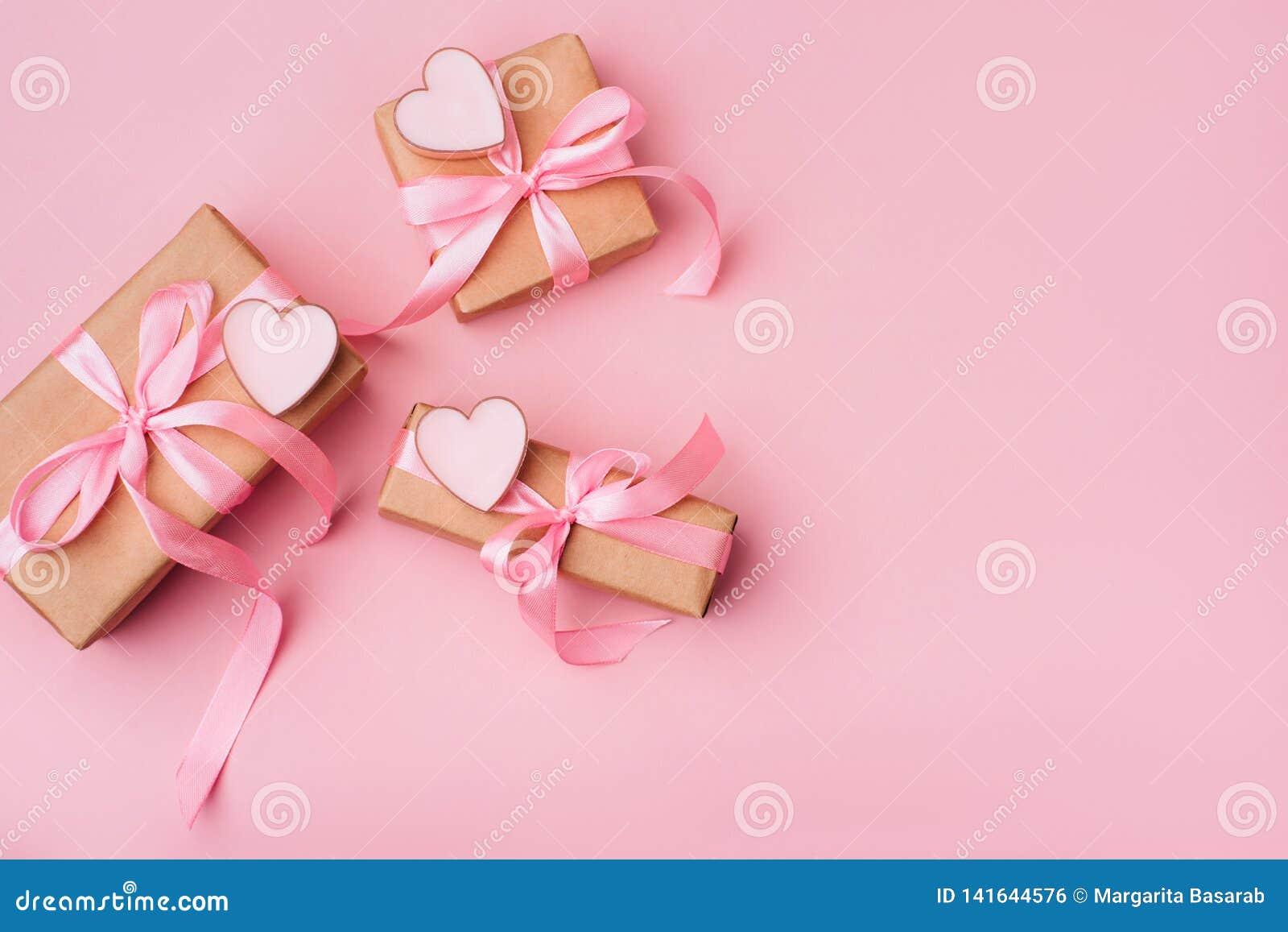 Composición del día de San Valentín: cajas de regalo blancas con el arco y los corazones rosados A