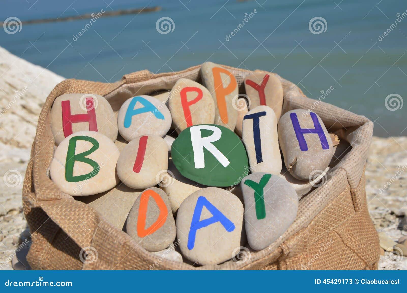 Composición del feliz cumpleaños de las letras de piedra en un bolso