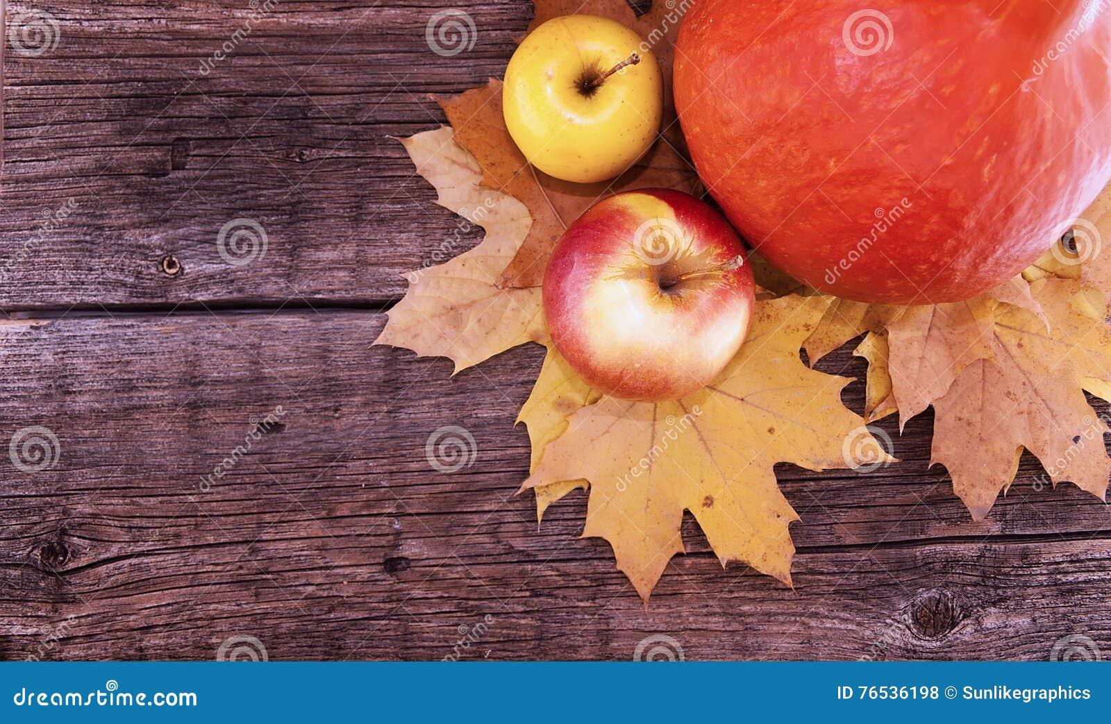 Composición del otoño con la calabaza, las hojas de arce amarillas y la manzana o