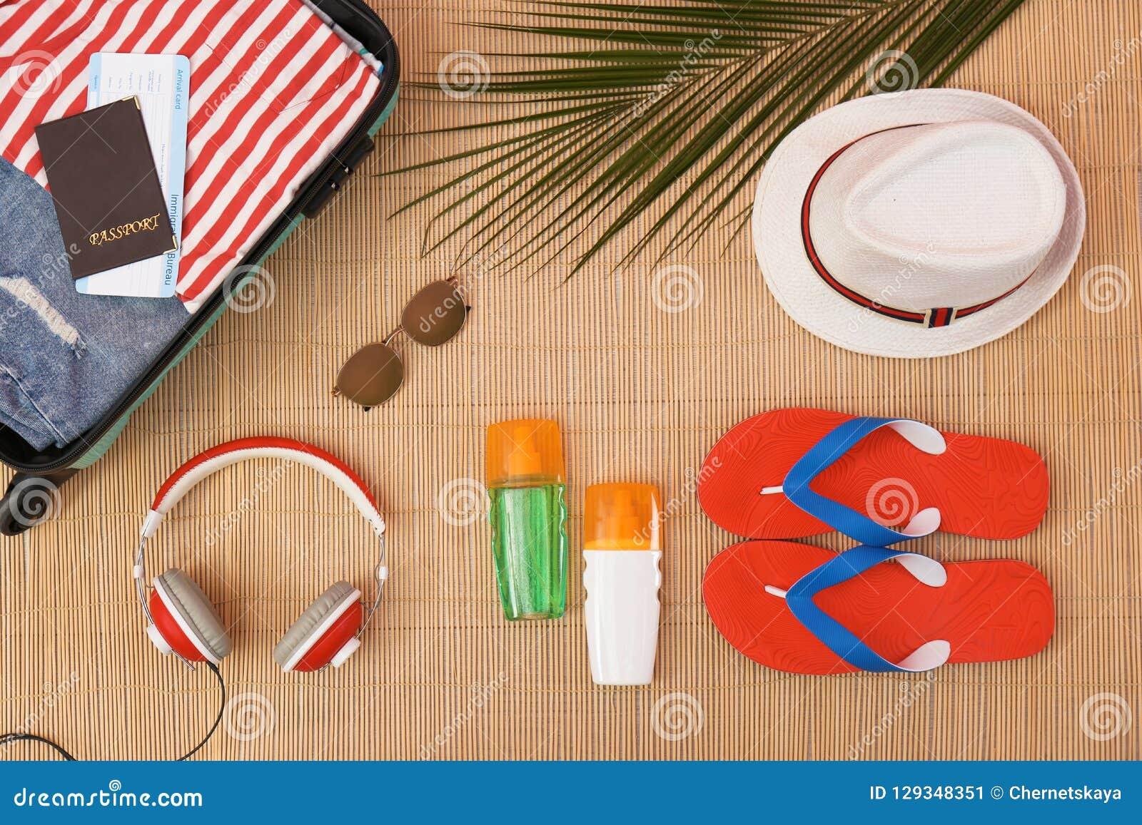 Composición plana de la endecha con los artículos abiertos de la maleta y de la playa