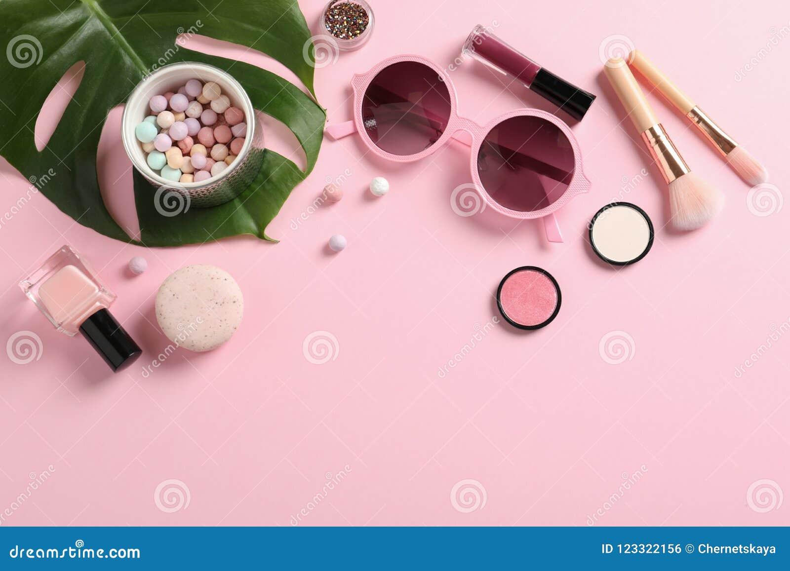 Composición plana de la endecha con los productos para el maquillaje decorativo en rosa en colores pastel