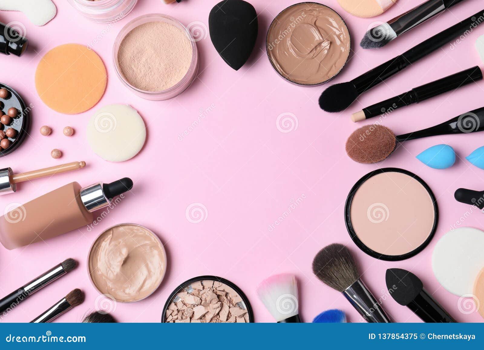 Composición puesta plana con la fundación de la piel, el polvo y los accesorios de la belleza en fondo del color