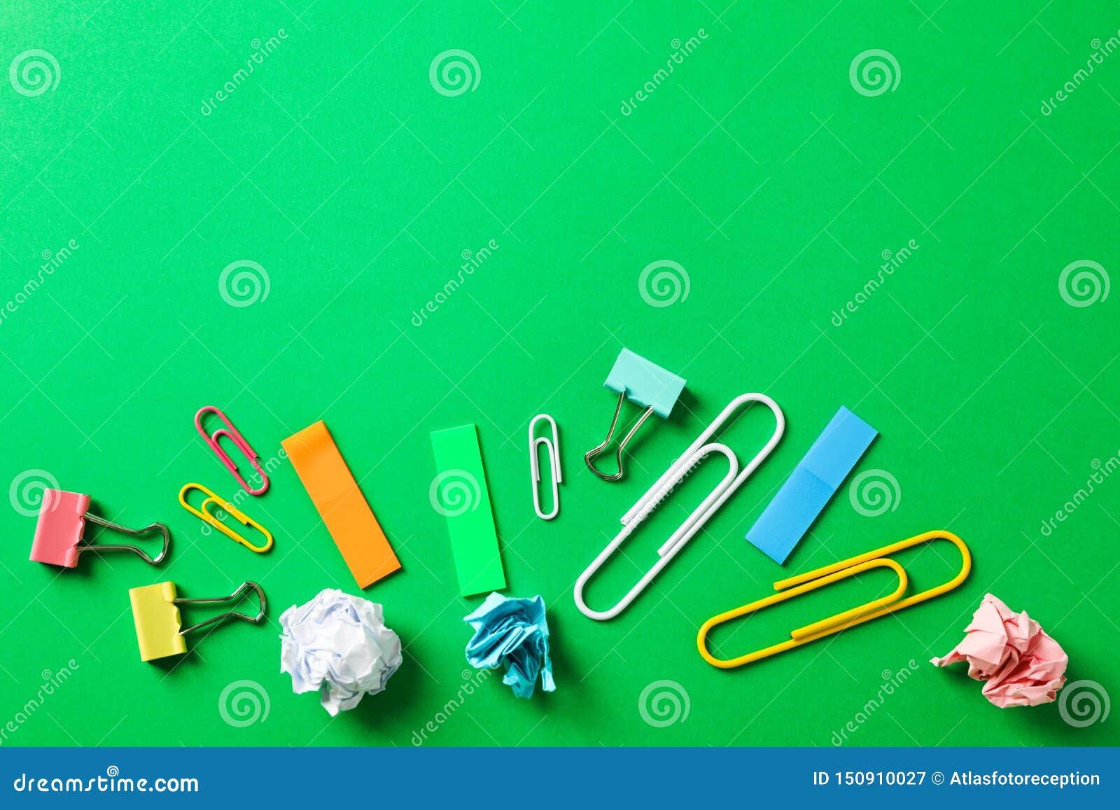 Composición puesta plana con las bolas de papel arrugadas, los clips y las etiquetas engomadas en fondo del color