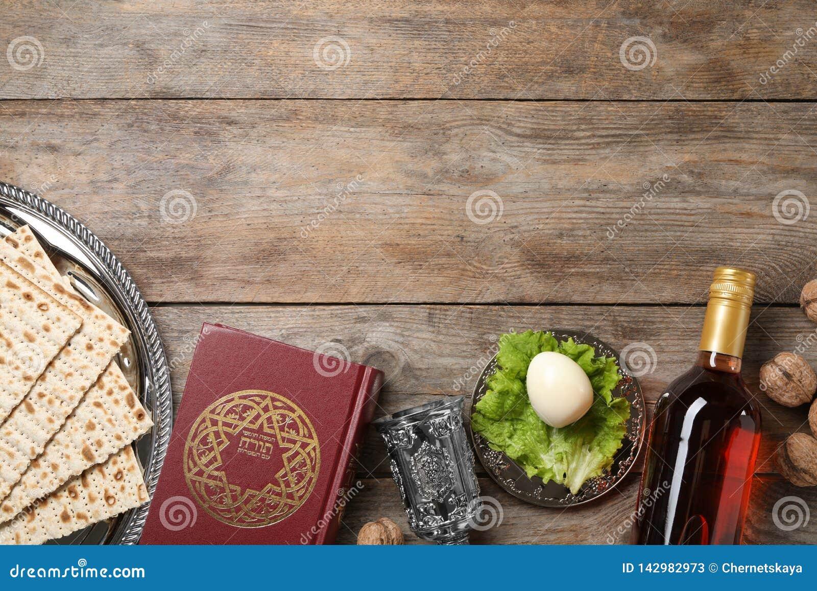 Composición puesta plana con los artículos simbólicos de Pesach de la pascua judía en fondo de madera