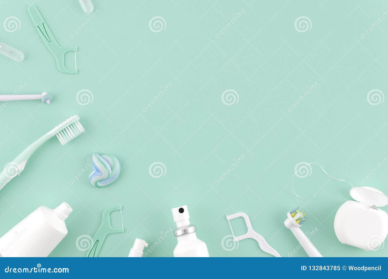 Composición puesta plana con los cepillos de dientes manuales y los productos de higiene oral en la mofa de Stomatologist del fon