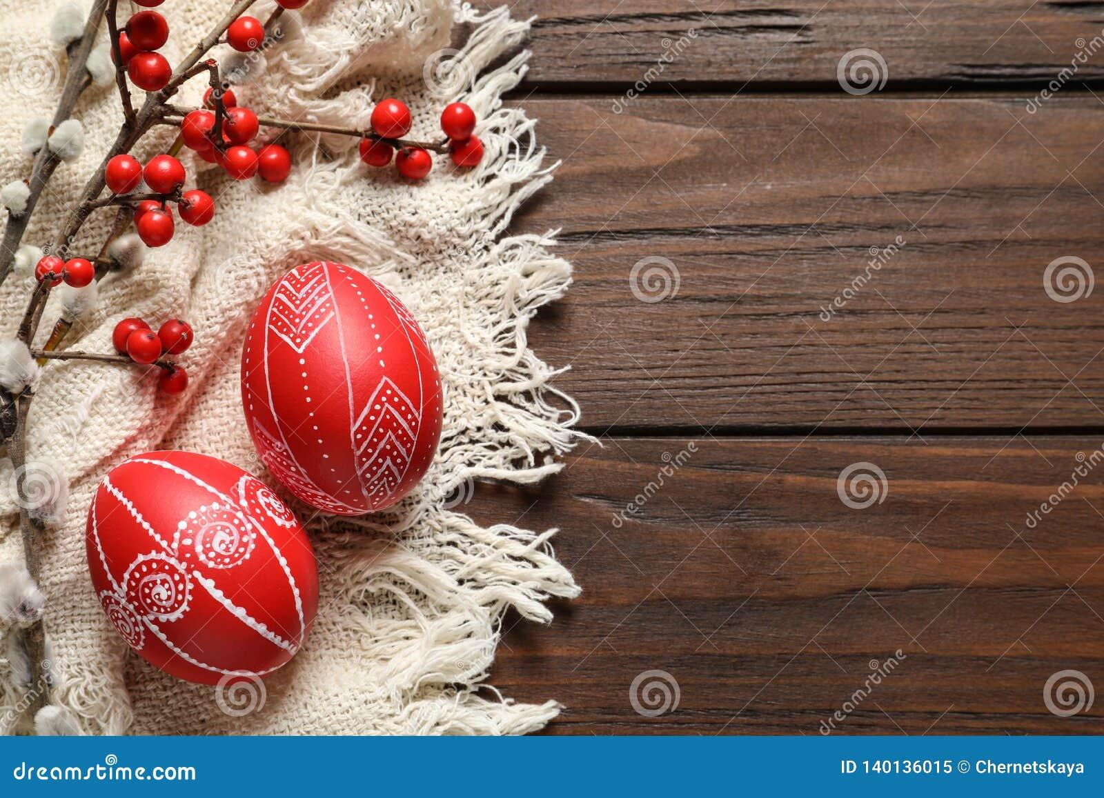 Composición puesta plana con los huevos de Pascua rojos pintados en la tabla de madera