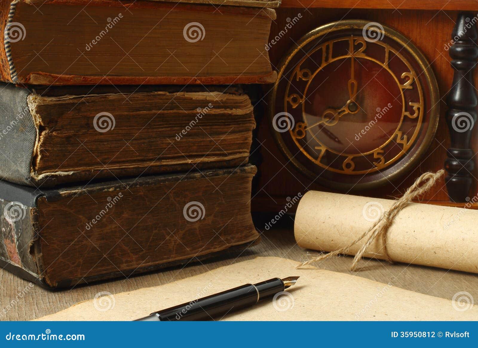 Composición retra con los libros, el reloj, el papel y la pluma