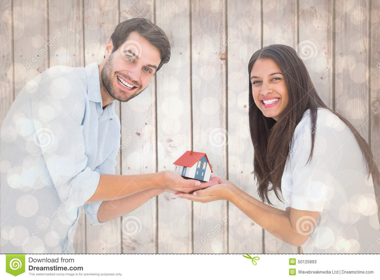 Composite image of attractive young couple holding a model house stock image image 50125893 - House plans for young couples energetic designs ...