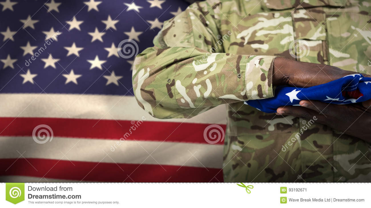 Composite image of mid section of soldier holding american flag