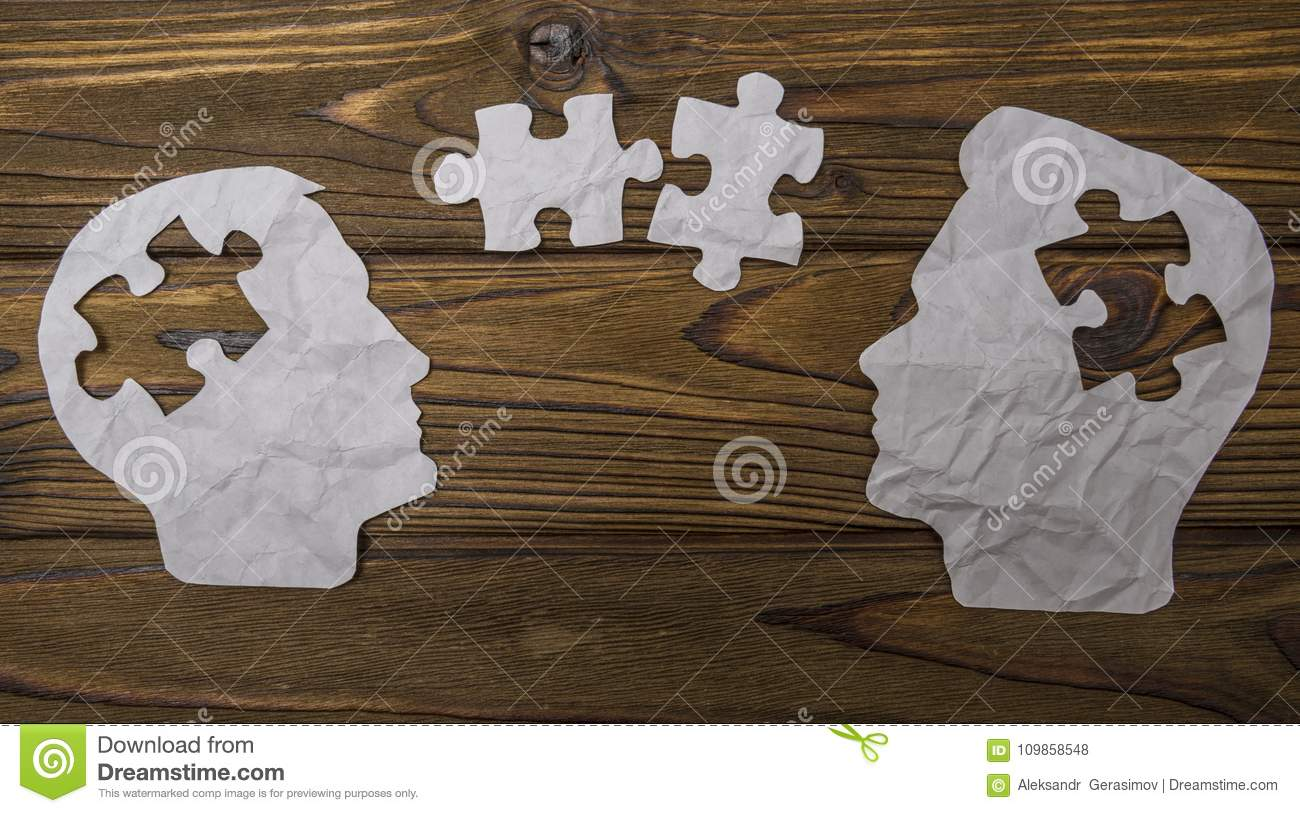 Composite image of paper in the form of two head silhouettes on a wooden background.