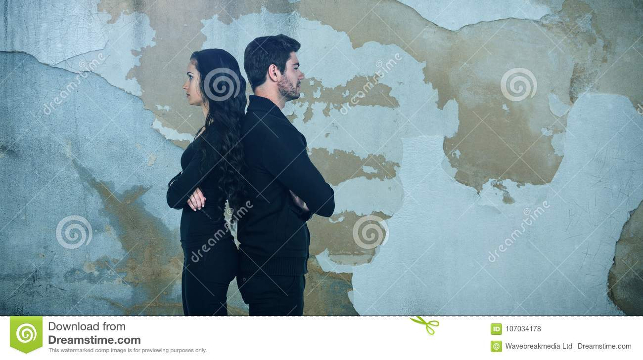 Composite image of profile view of sad couple standing back to back