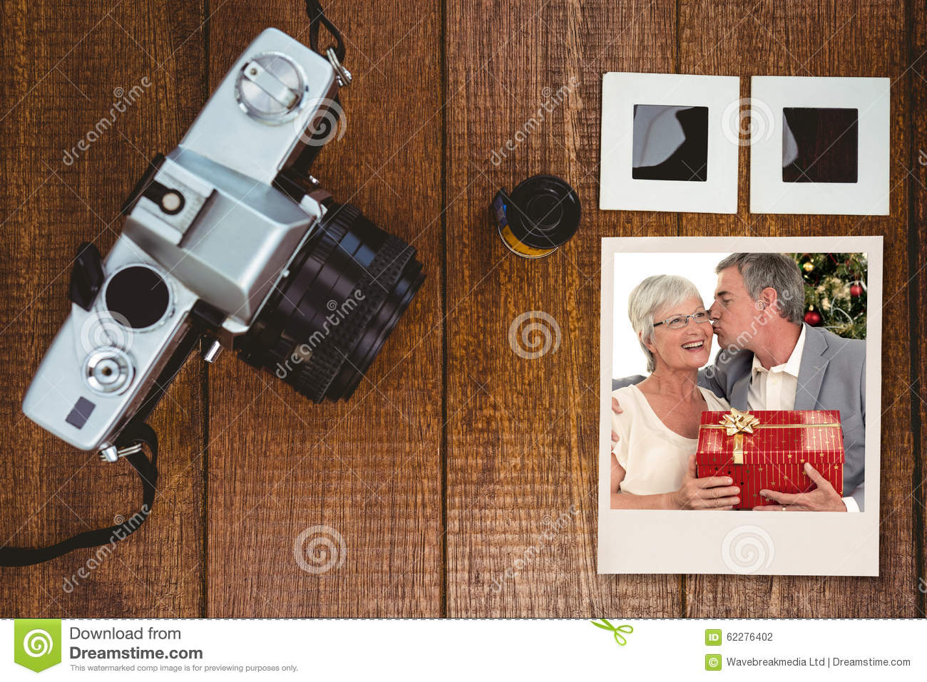 Composite image of senior man giving a kiss and a christmas present to his wife