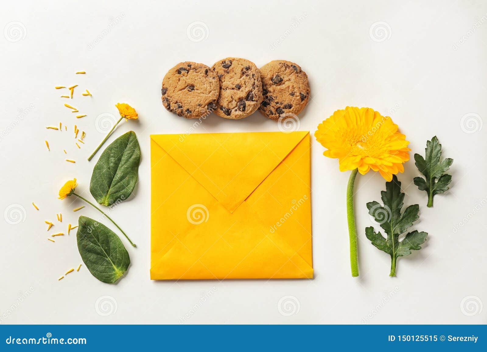 Composition étendue plate avec des fleurs, des biscuits et l enveloppe sur le fond blanc