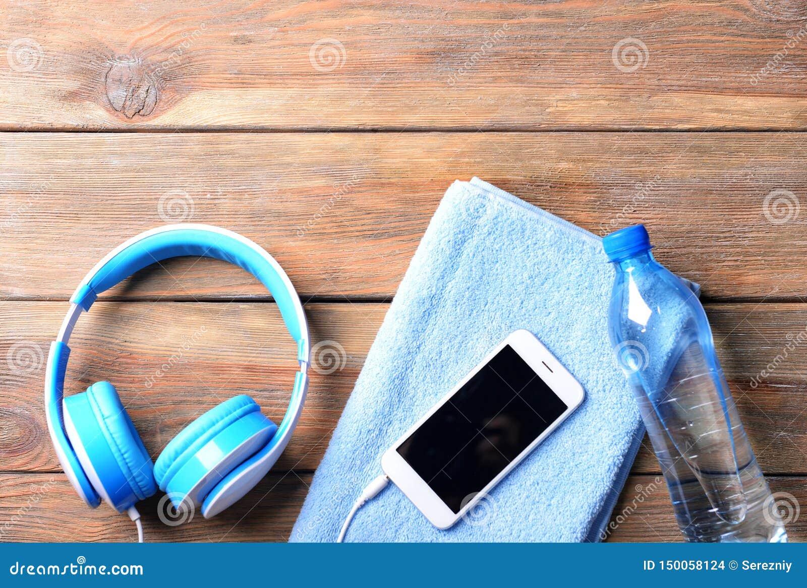 Composition étendue plate avec le smartphone, la bouteille de l eau, la serviette et les écouteurs sur le fond en bois S?ance d e