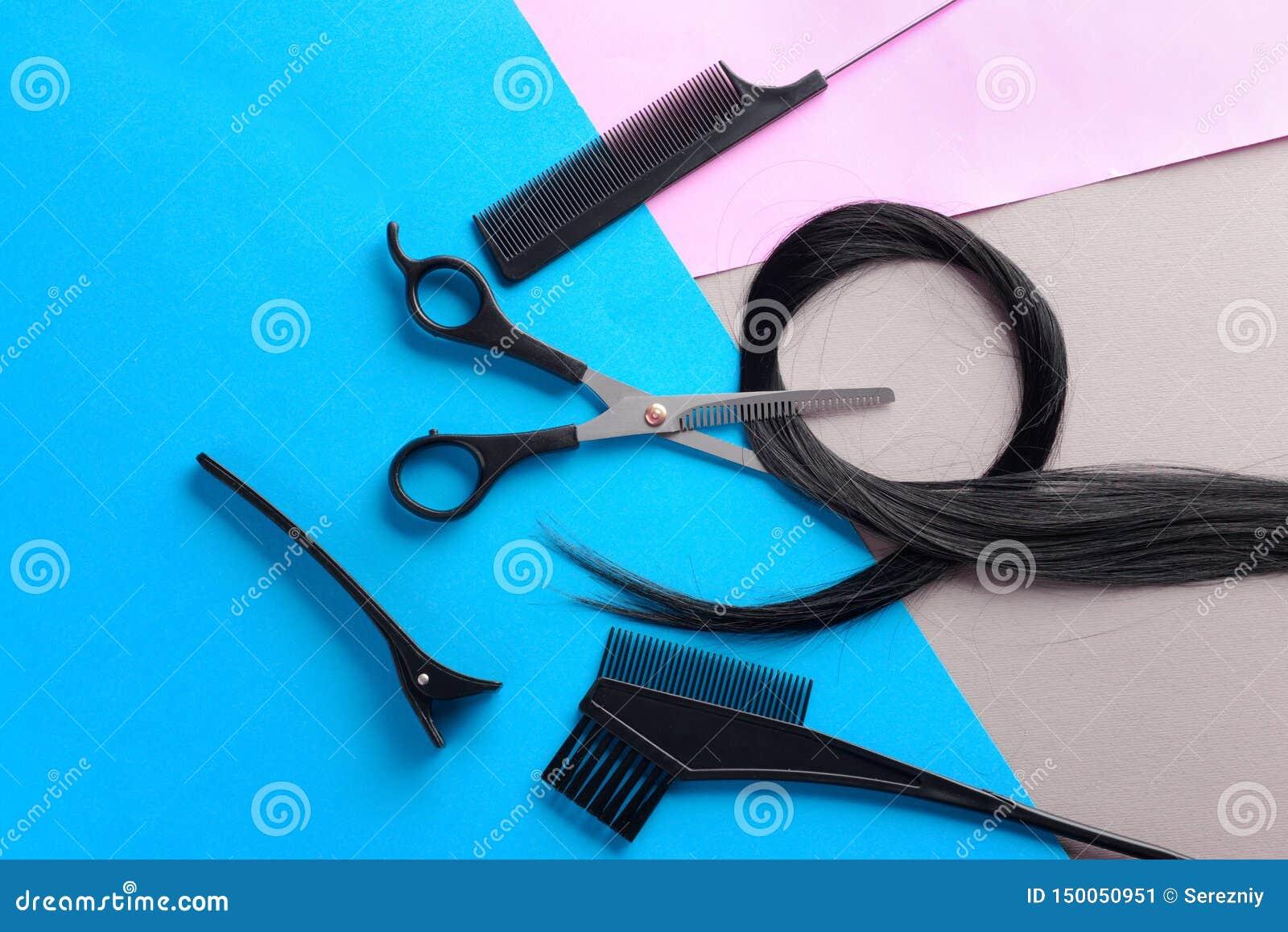 Composition étendue plate avec les outils et la mèche du coiffeur des cheveux noirs sur le fond de couleur