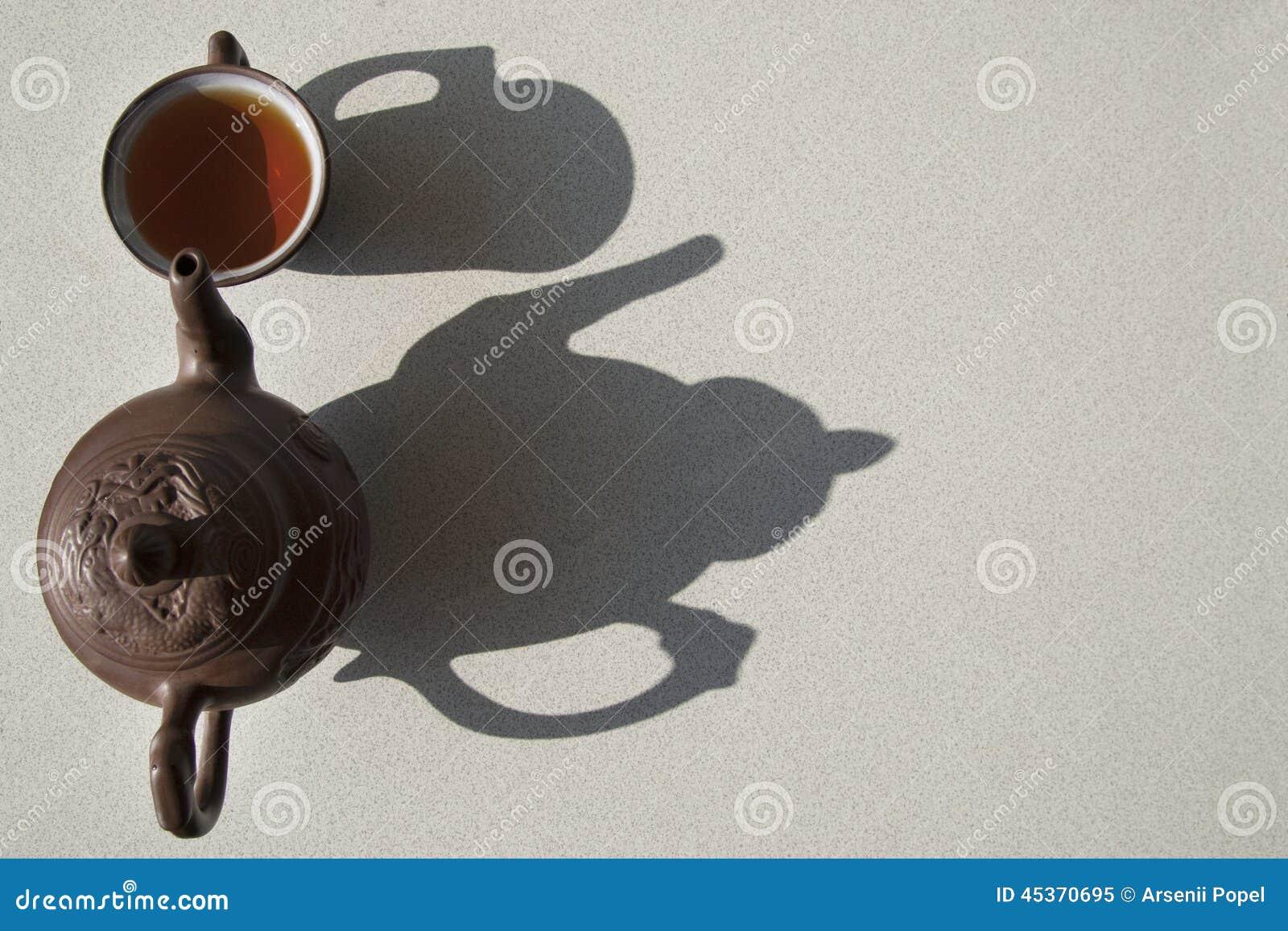 Composition avec le thé dans la tasse et la théière sur la table