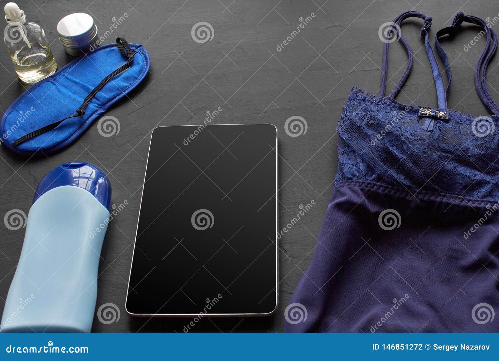 Composition avec les produits cosm?tiques de soins de la peau sans label et lingerie blanche sur un fond de bureau noir