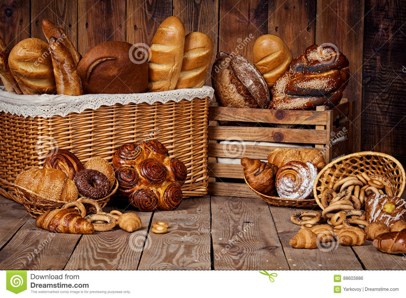 Composition with bread and rolls in wicker basket.