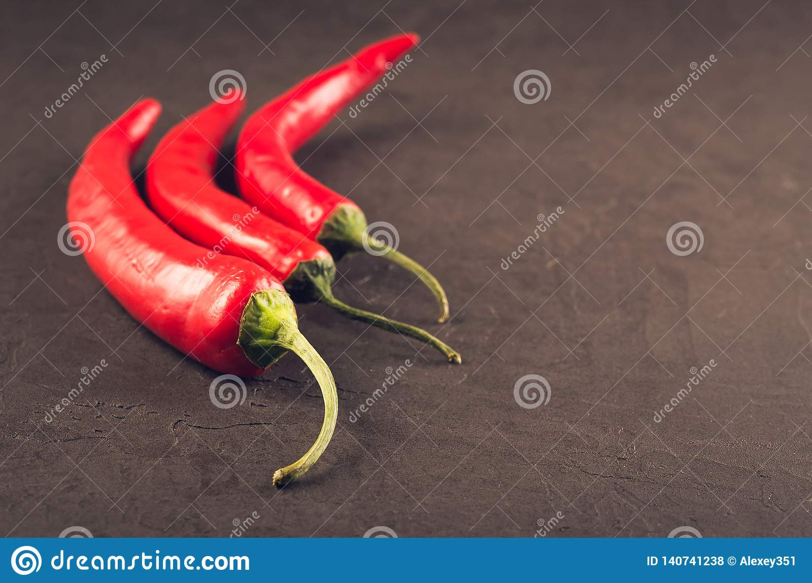 Composition of chili pepper/red hot Chile pepper on a dark stone background. Selective focus and copyspace