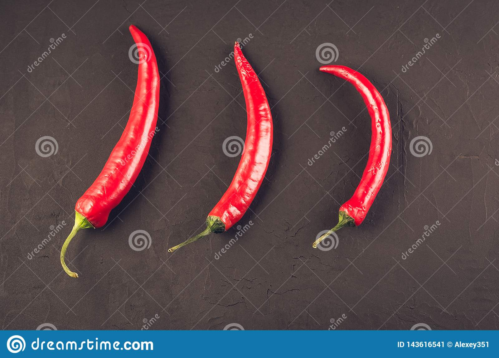Composition of chili pepper/red hot Chile pepper on a dark stone background. Top view