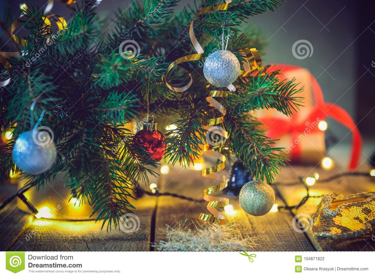 composition of christmas tree in vase with decorations gifts and lights on the wooden vintage