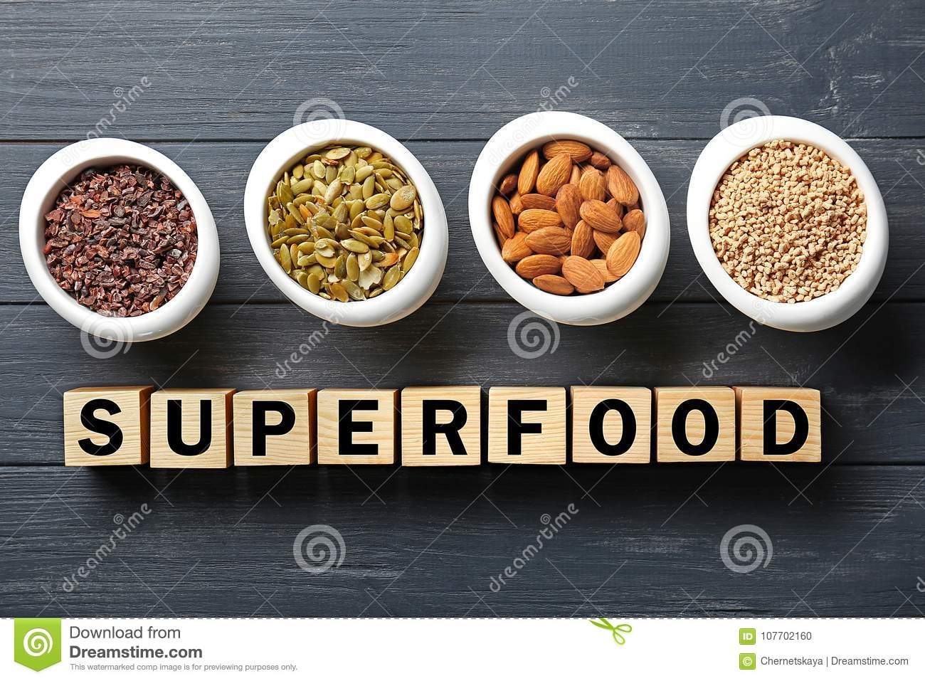 Composition with cubes and assortment of superfood products in bowls on wooden background,
