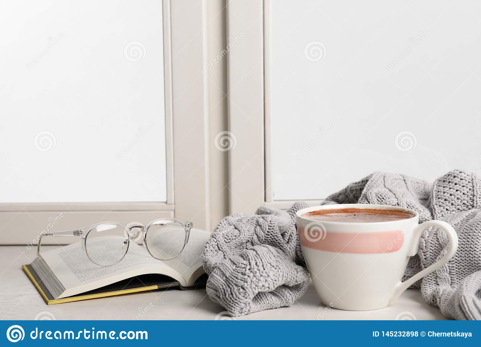 Composition with cup of hot chocolate and book on windowsill, space for text