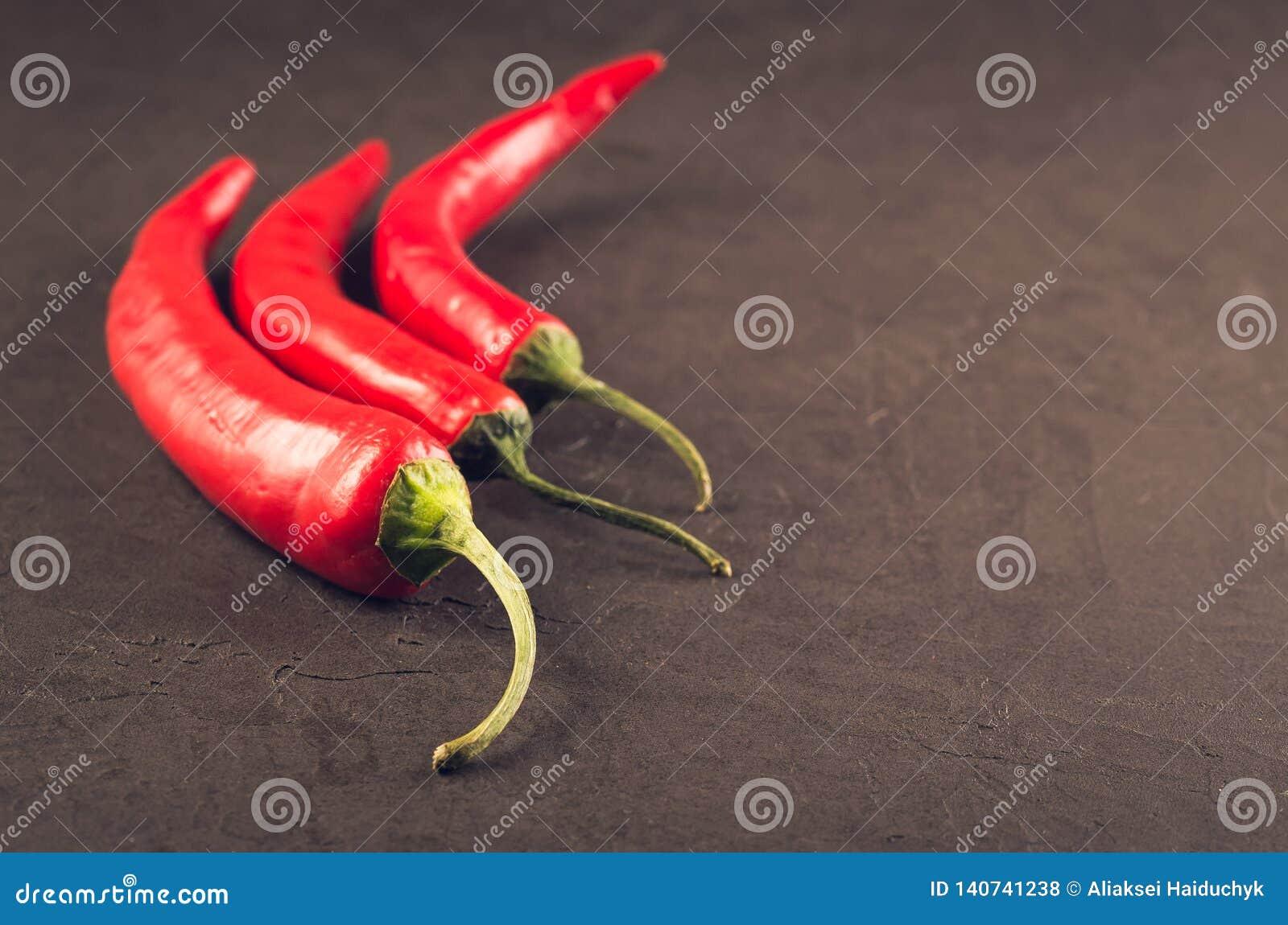 Composition de poivre de piment/de poivre d un rouge ardent du Chili sur un fond en pierre foncé Foyer sélectif et copyspace