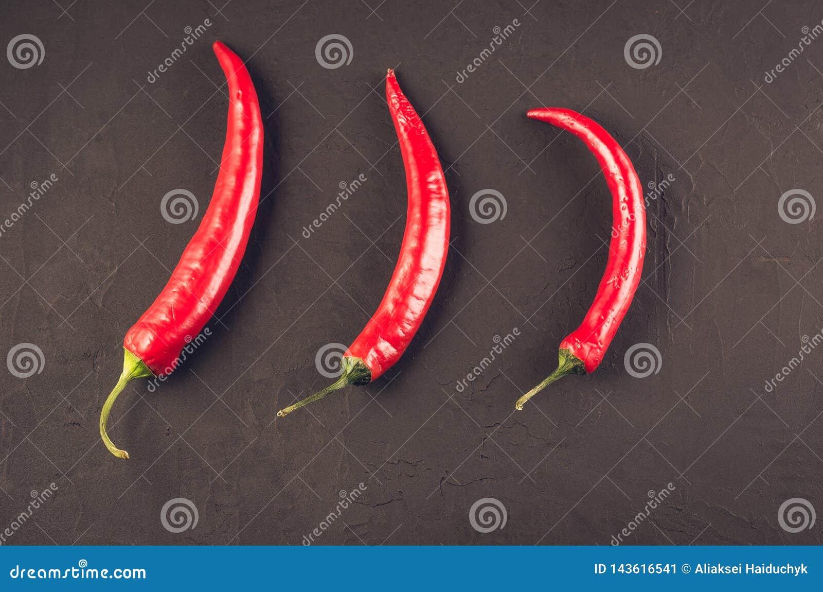 Composition de poivre de piment/de poivre d un rouge ardent du Chili sur un fond en pierre fonc? Vue sup?rieure