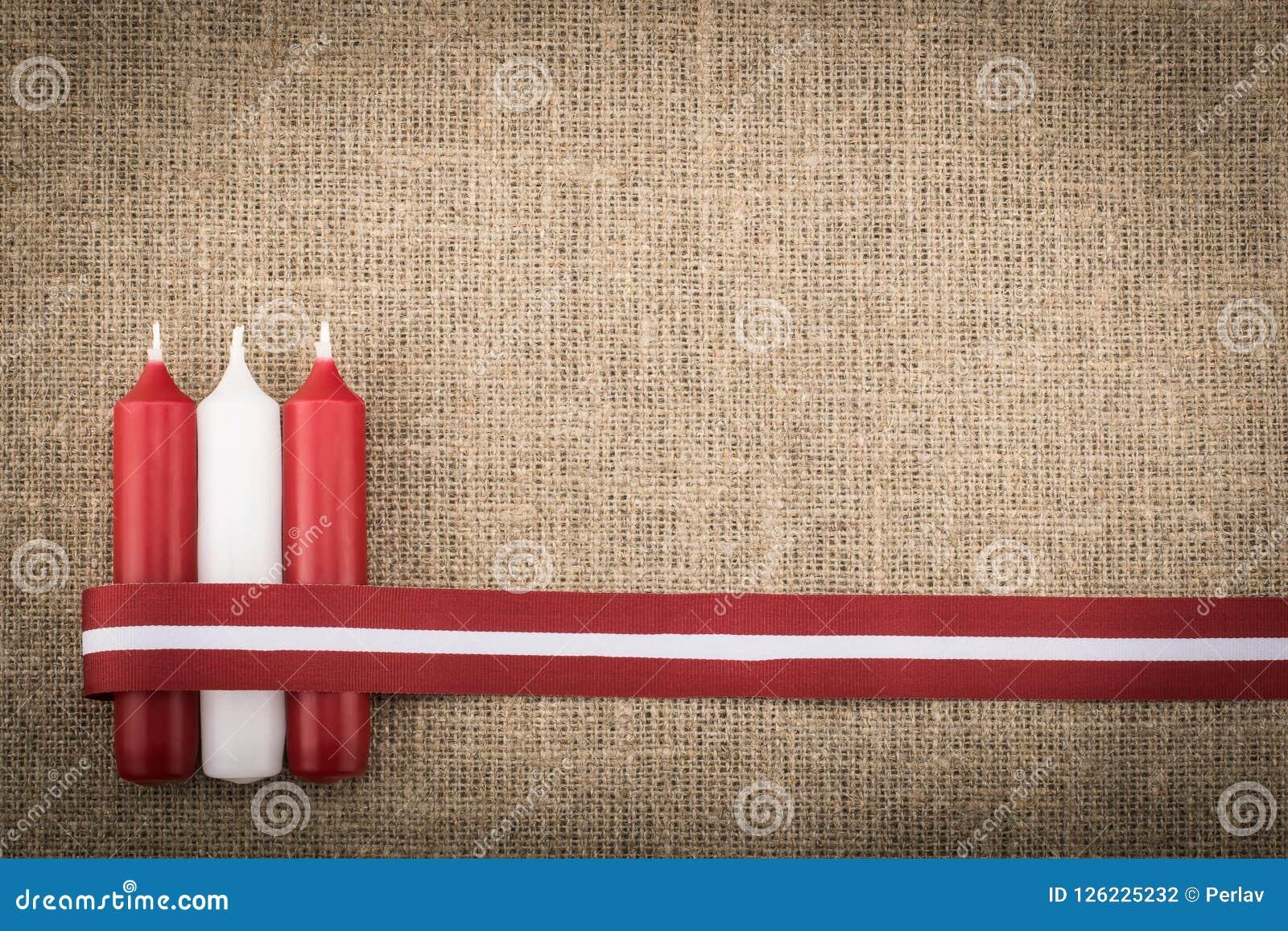 Composition de trois bougies blanches rouges et de ruban letton de drapeau