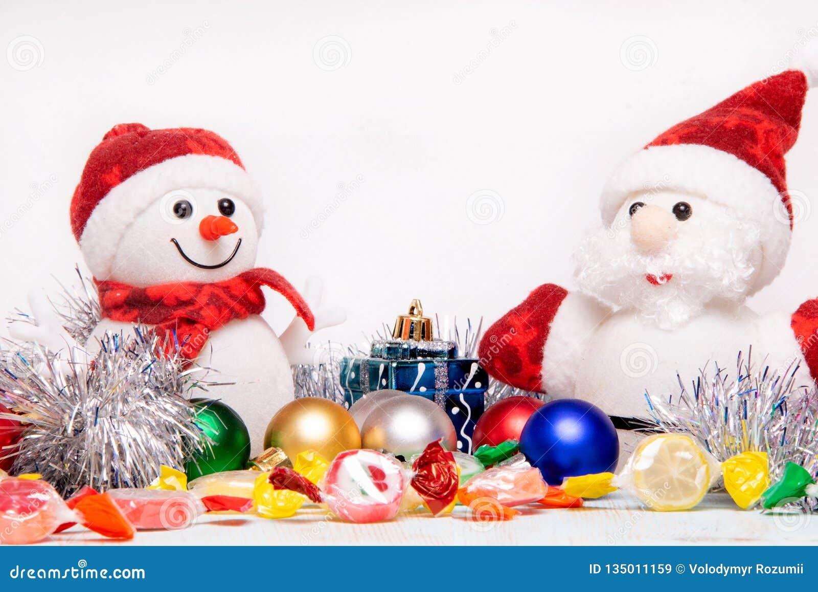 Composition en beau Noël et en nouvelle année avec Santa Claus et le bonhomme de neige dans les chapeaux et des écharpes rouges d