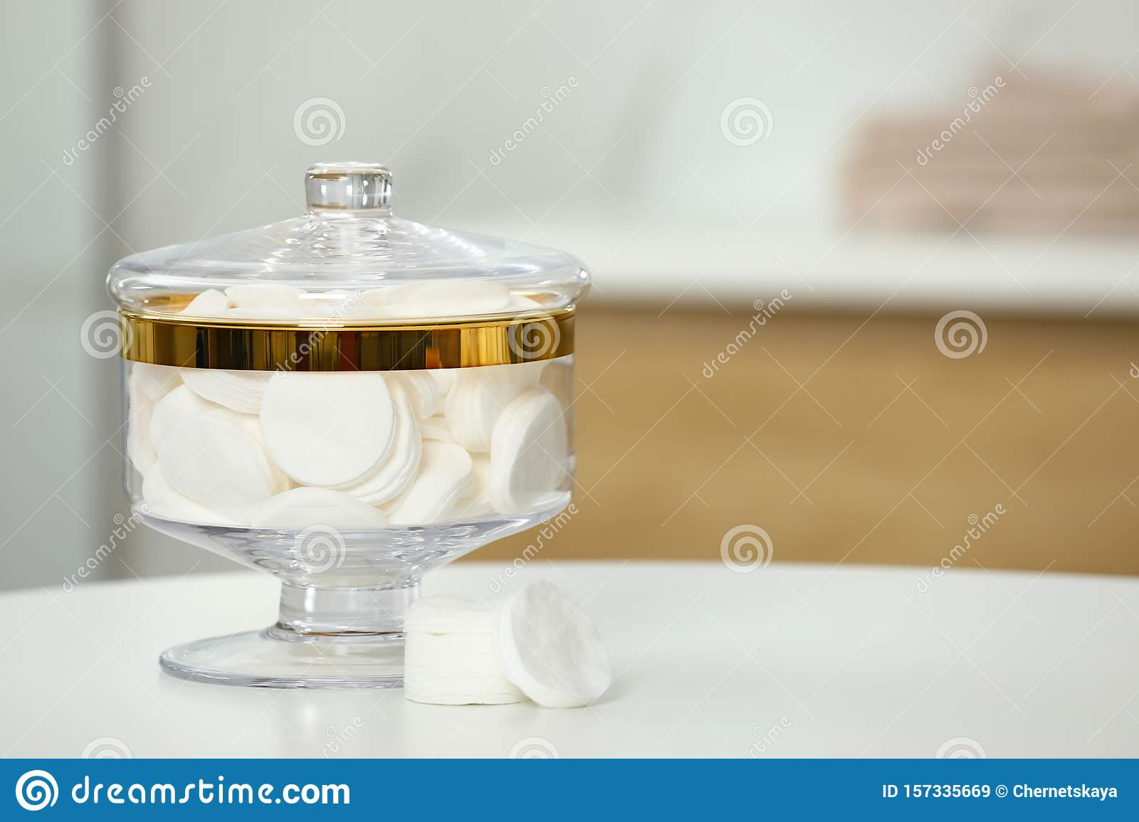 Composition of glass jar with cotton pads on table in bathroom