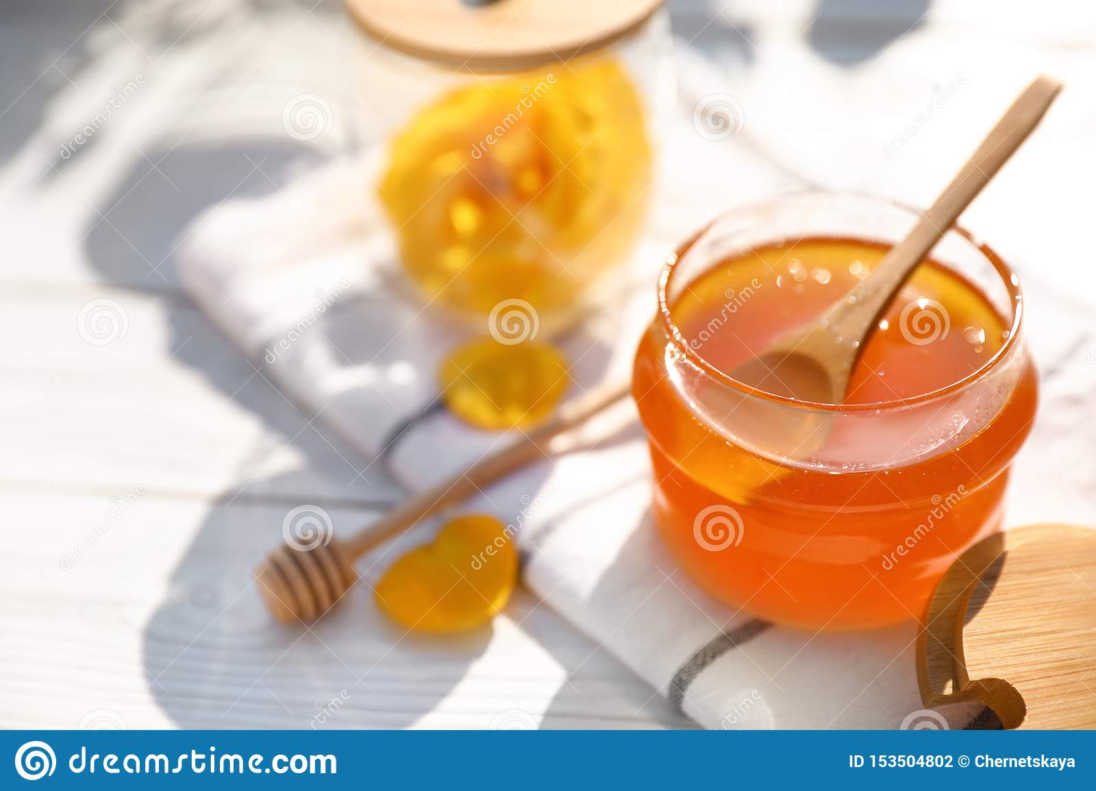 Composition with glass jar of fresh rose honey on white wooden table