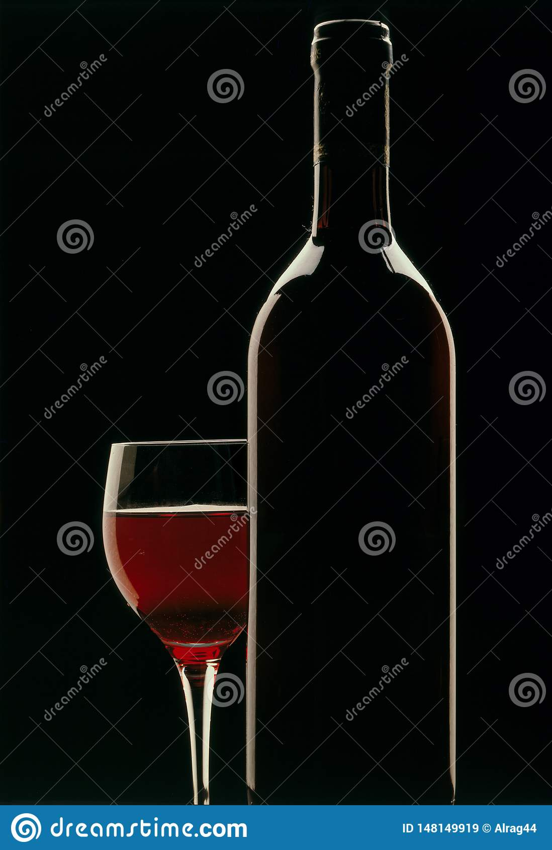 Glass of red wine with bottle