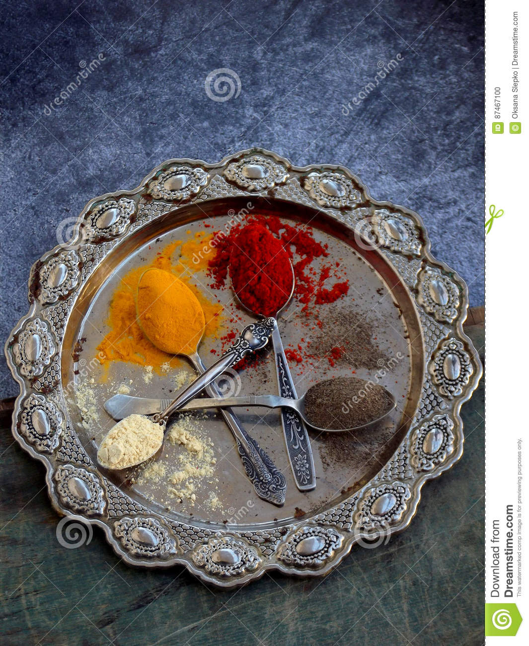 The composition of ground spices in a spoon on a metal dish. Paprika, turmeric, ginger, black pepper. Top view