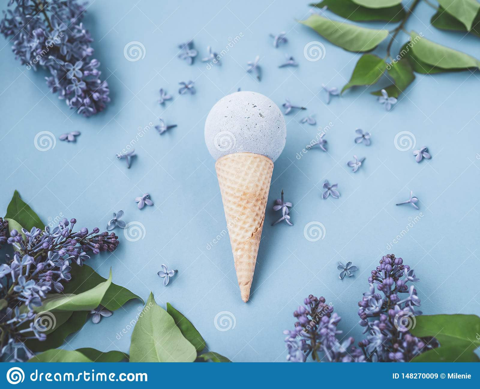 Composition of ice cream cone with bath ball on a blue background