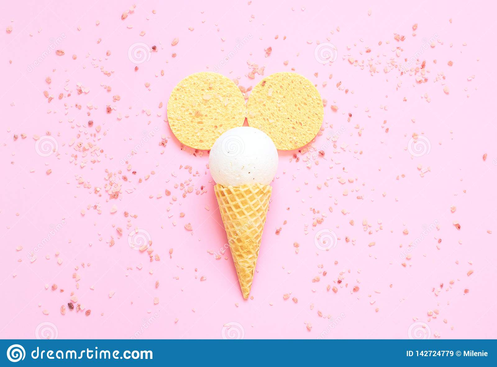 Composition of ice cream cone with bath ball on a light pink background
