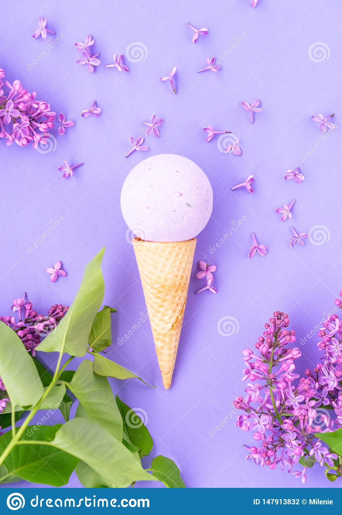 Composition of ice cream cone with bath ball on a violet background. Bathroom cosmetic accessories