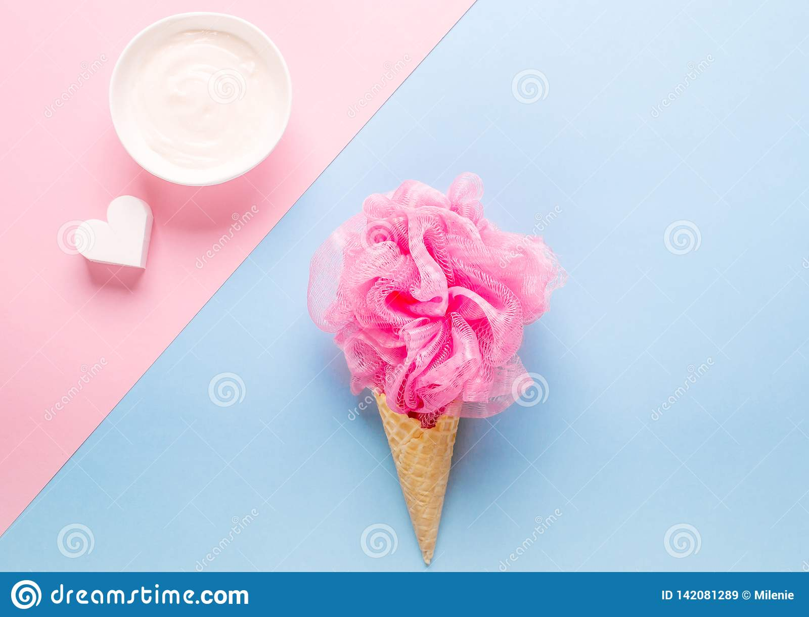 Composition of ice cream cone with pink wisp of bast on a light blue background