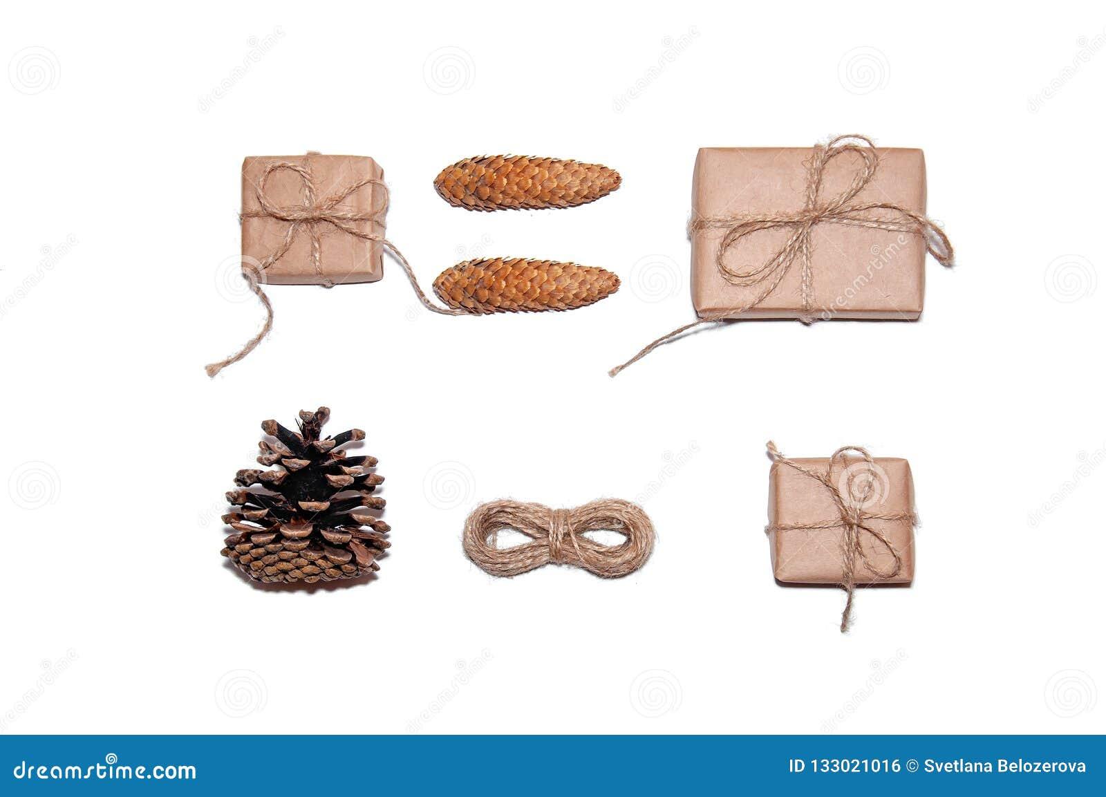 Composition minimale en Noël Boîte-cadeau, cônes de pin, corde sur le fond blanc Concept de vacances de nouvelle année Configurat