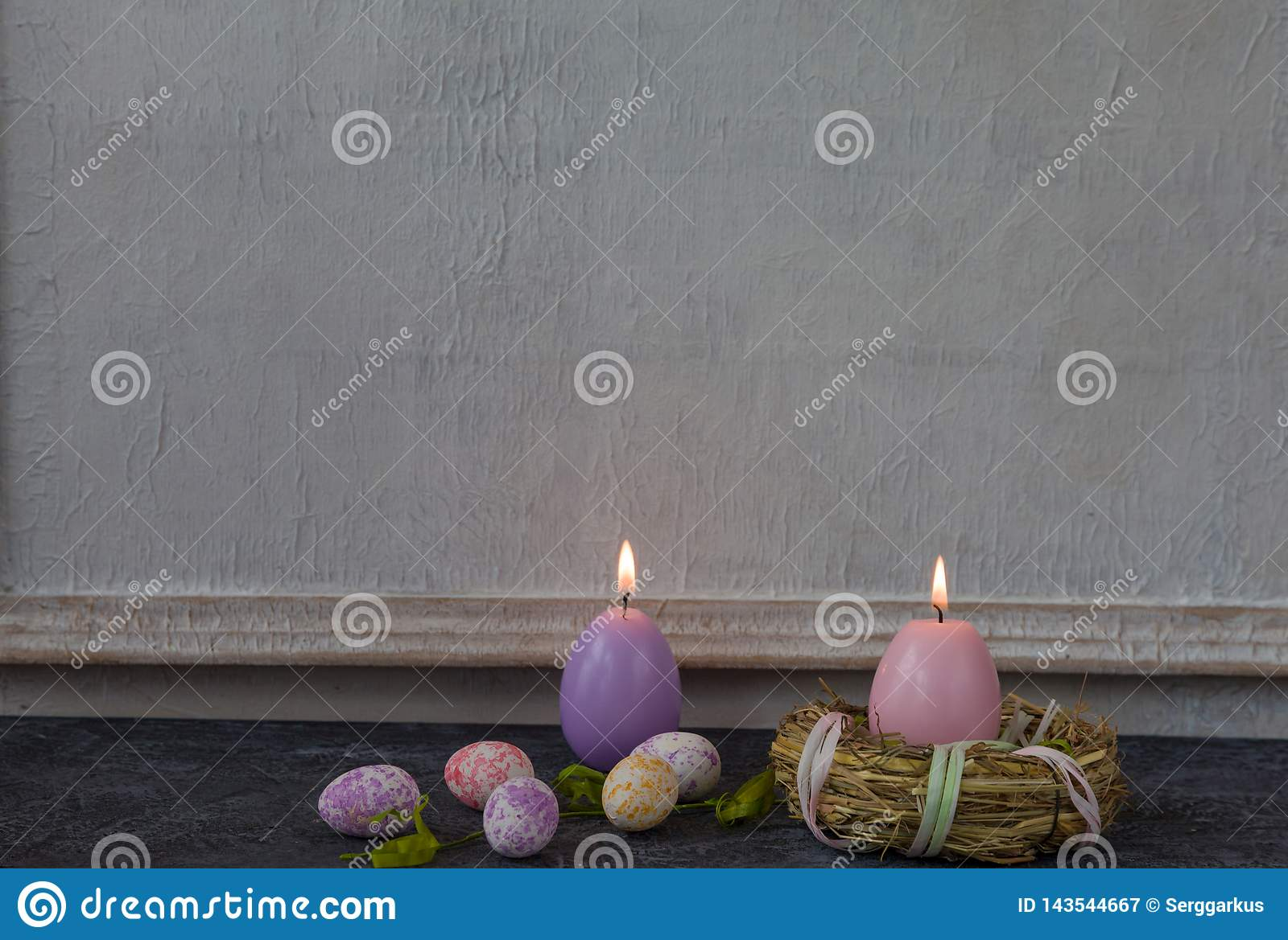Composition of painted Easter eggs on dark stone table and vintage white wall background
