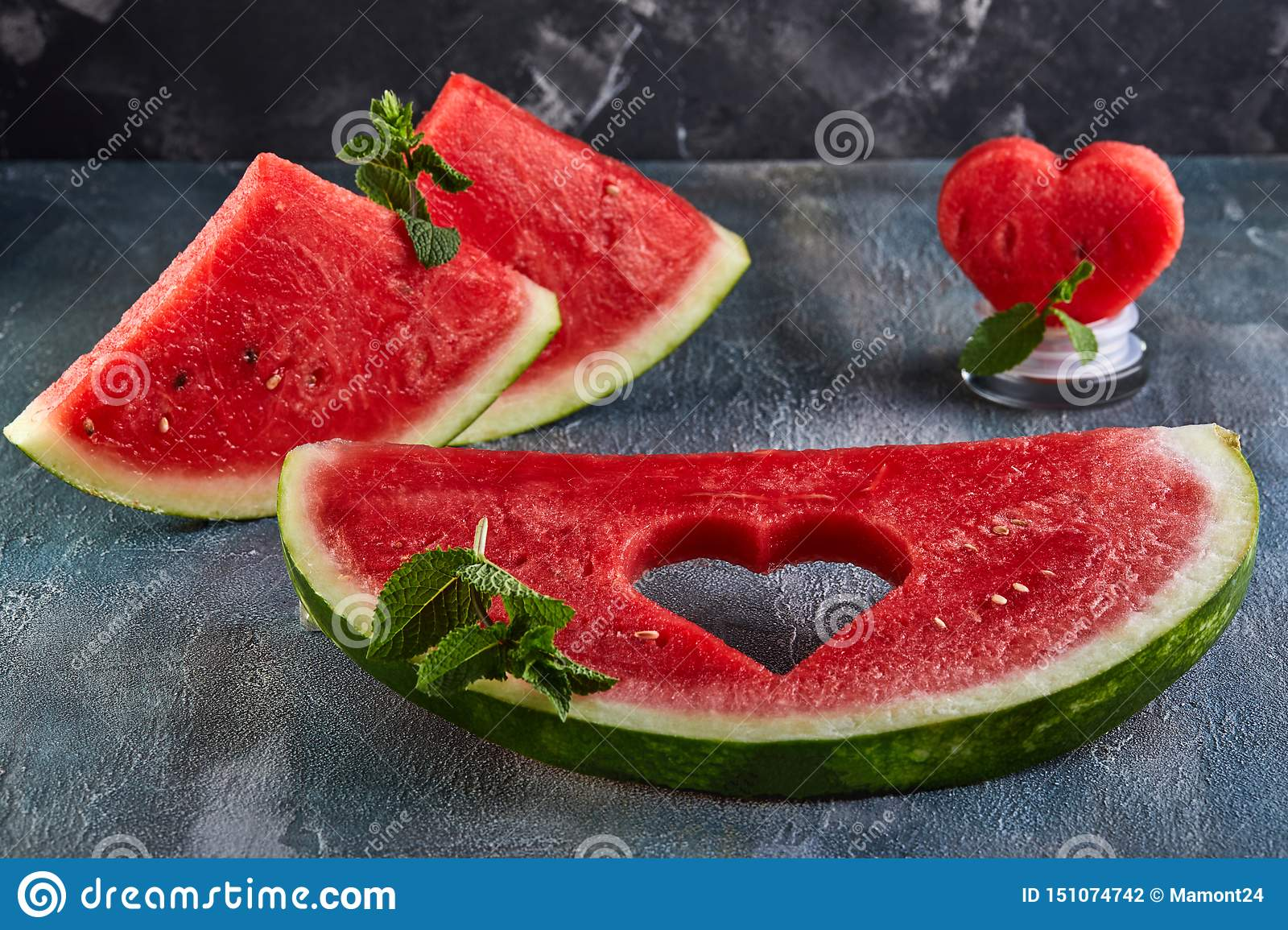 Composition with ripe watermelon, mint leaves and a heart carved in a slice of watermelon. Concept for valentines day
