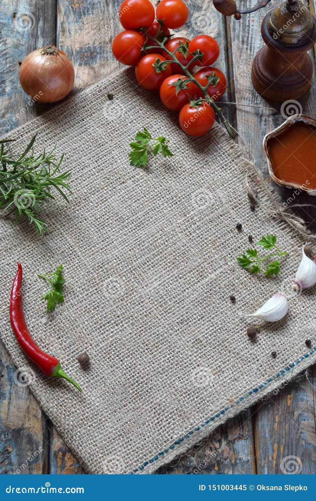 Composition rustique avec le moulin de poivre, le souce de tomate, les herbes fraîches, les légumes et les épices Style campagnar