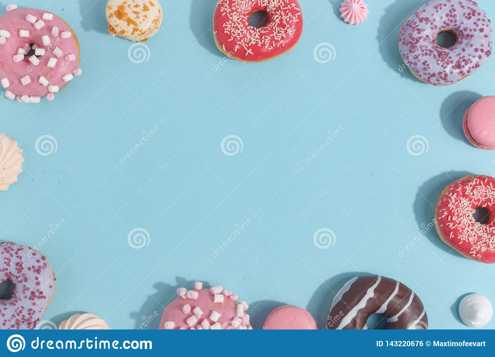 Composition of sweet glazed donuts and sweets on a blue background. Top view. Concept of children's holiday. Space for copy