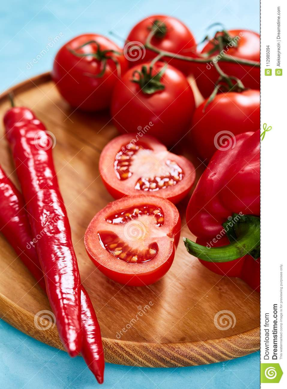Composition of tomato bunch and halves and sweet pepper on wooden plate, top view, close-up, selective focus.
